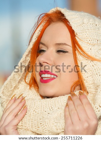 Winter fashion. Beauty face portrait red hair young woman in warm clothing white hood on head outdoor enjoying sunlight on sunny day. - stock photo