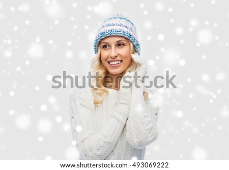winter, fashion, christmas and people concept - smiling young woman in winter hat, sweater and gloves