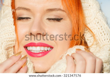 Winter fashion. Close up beauty face portrait red hair young woman in warm clothing white hood on head outdoor enjoying sunlight on sunny day. - stock photo
