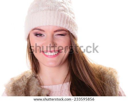 Winter fashion. Portrait positive teen girl in warm clothes. Happy woman in cap winking, positive face expression isolated