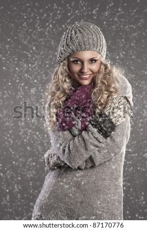 winter fashion shot of a smiling attractive blonde wearing a wool cap, a grey wool sweater, gloves and a purple scarf - stock photo