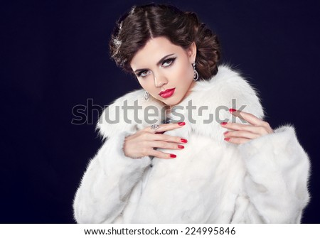 Winter Fashion woman in fur coat, elegant brunette lady portrait. Makeup. Manicured nail. Isolated on dark background. - stock photo