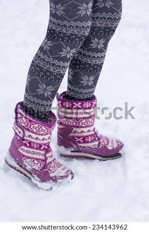 winter female feet in boots and stockings with a pattern in the snow