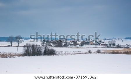 Winter field landscape under cloudy sky near small village. Polish countryside - stock photo