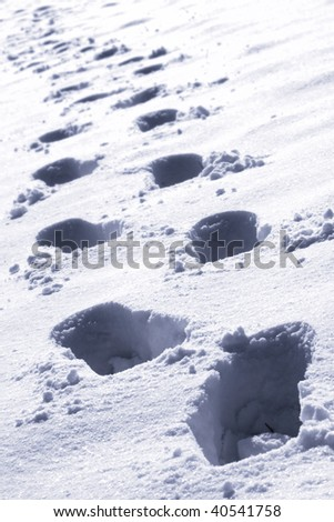 winter - footprints in white snow - in blue shade colours - stock photo