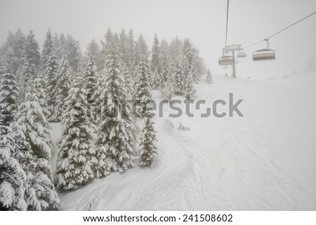 Winter forest and chairlift in snowfall at alpine ski resort - stock photo