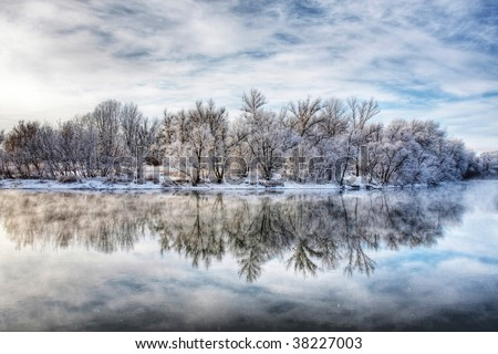 Winter forest river with reflection of the sky - stock photo