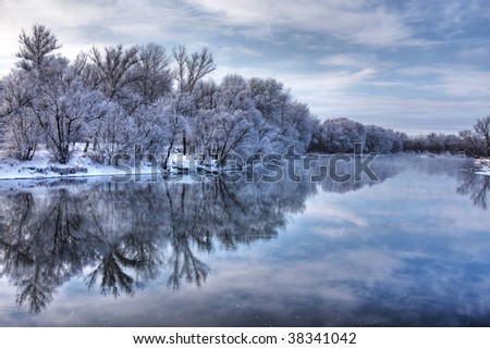Winter forest river with reflection of the sky
