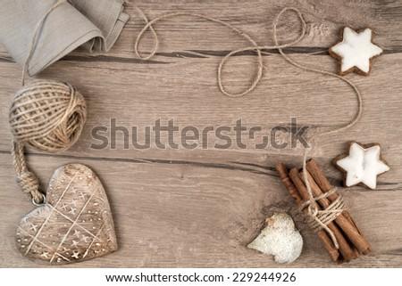 Winter frame on wood: Christmas cookies, cinnamon, cord, linen napkin and wooden heart. Space for your text - stock photo