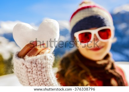 Winter fun, beautiful young girl with heart of snow  - stock photo