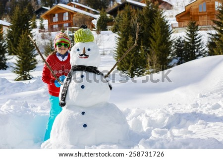 Winter fun, happy girl playing with snowman with a mustache - stock photo