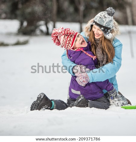 Winter fun, winter vacation concept. Happy mother and son in winter park having fun. focus on mother - stock photo