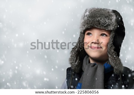 Winter fur hat clothing boy is looking up at snowfall - stock photo