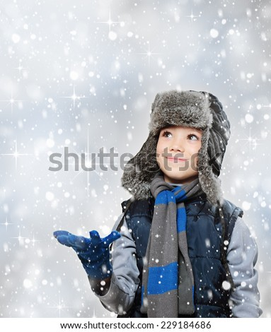 Winter fur hat clothing boy with outstretched hand and looking snow falling - stock photo