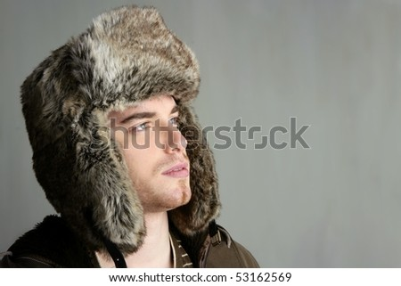winter fur hat portrait of fashion young handsome man - stock photo