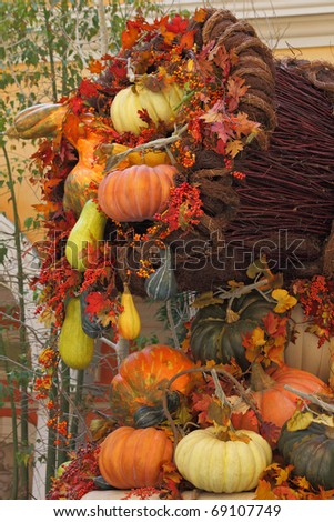 Winter garden in a lobby of magnificent hotel. A harvesting holiday: baskets and vases with multi-colored pumpkins, flowers and autumn leaves