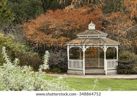 Winter garden scene with white wooden gazebo, surrounded by lots of nature - stock photo