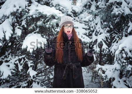 Winter girl and snow fir tree. Beautiful young woman in glasses