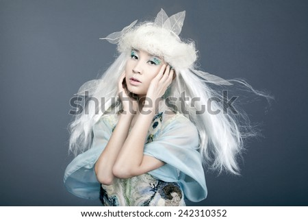 Winter girl Portrait. Snow.  Young beautiful fashion Model woman with White Hair. Make up. Asia Snow Queen - stock photo