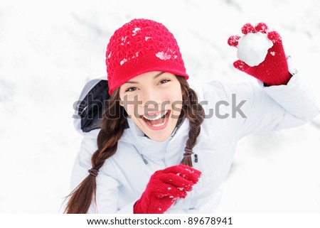 winter girl throwing snowball at camera smiling happy having fun outdoors on snowing winter day playing in snow. Cute playful multicultural Asian Caucasian young woman outdoor enjoying first snow. - stock photo