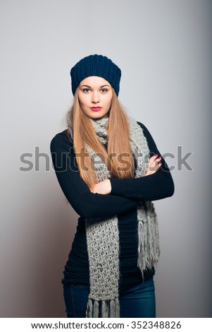 Winter girl waiting for something with his arms crossed. Lifestyle studio photo isolated portrait of a woman on a gray background. - stock photo
