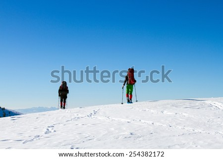 Winter hiking in the mountains on snowshoes with a backpack and tent.