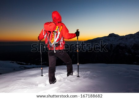 Winter hiking: man stands on a snowy ridge looking at the sunset (point-and-shoot camera style version). South Alps mountain  landscape. Italy, Europe. - stock photo