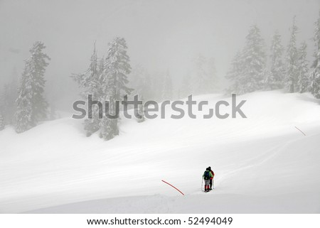 Winter hiking view while hikers cross snow field. - stock photo