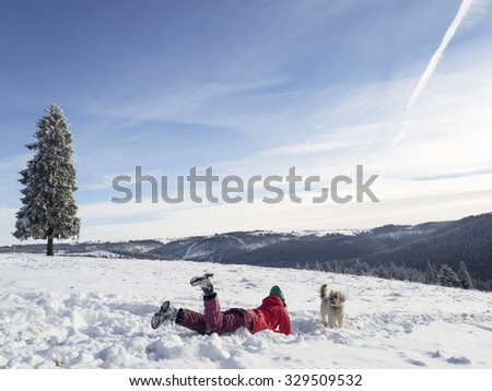 Winter holiday fun. Girl  playing with dog in the snow  - stock photo