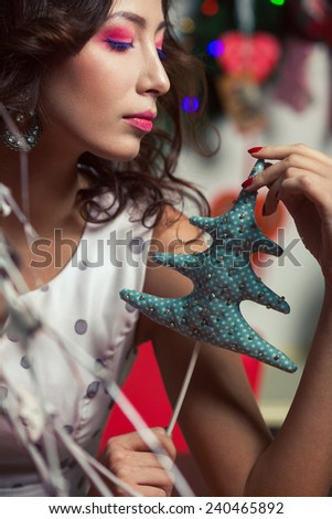 Winter holidays celebration concept. Portrait of doll like brunette holding soft handmade toy - christmas tree - in restaurant, cafe. Homemade decoration. Close up. Vintage style. Indoor shot - stock photo