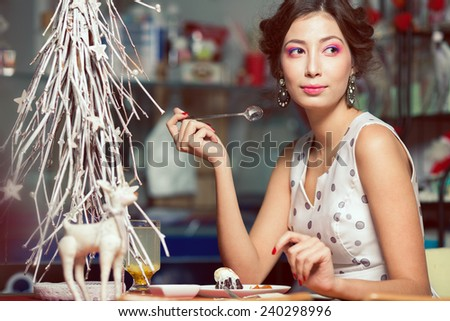 Winter holidays celebration concept. Portrait of doll like brunette in retro polka-dot sleeveless dress drinking tea, eating cake in restaurant. White christmas tree decoration. Close up. Indoor shot - stock photo