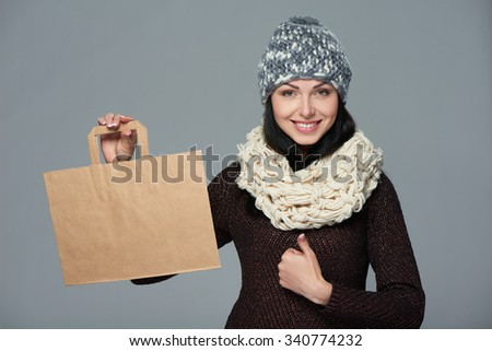 Winter holidays sale, shopping, Christmas concept. Portrait of smiling woman wearing warm winter hat and muffler showing shopping bag with empty copy space and gesturing thumb up - stock photo