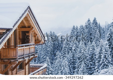 winter holidays, ski vacations background, wooden house under snow in the Alps - stock photo