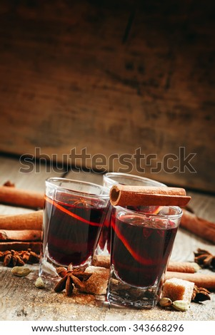 Winter hot mulled wine with cinnamon, star anise, orange and brown cane sugar in a small glass on the old wooden background, selective focus - stock photo