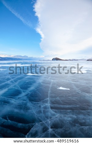 Winter ice landscape on Siberian lake Baikal with dramatic weather clouds front before the Storm