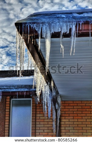 Winter icicles hanging from eaves of roof - stock photo