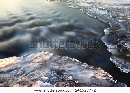 Winter icy stream at sunset, long exposure. Beautiful Christmas card.  - stock photo