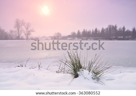 Winter lake and red sunset in misty evening. Composition of nature. - stock photo