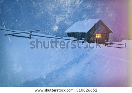 Winter landscape at night. Wooden house with a light in the window. Trail in the snow. Christmas view. Color toning. The effect of old photos from scuffs and scratches