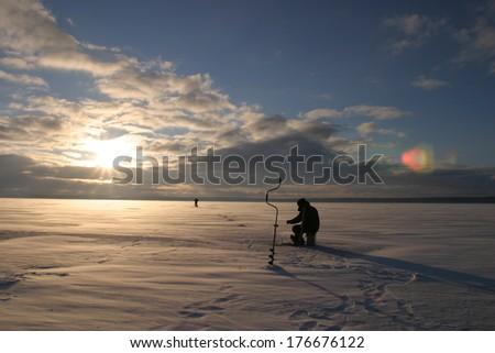 winter landscape fisherman fishing on the estuary Eek river at sunset - stock photo
