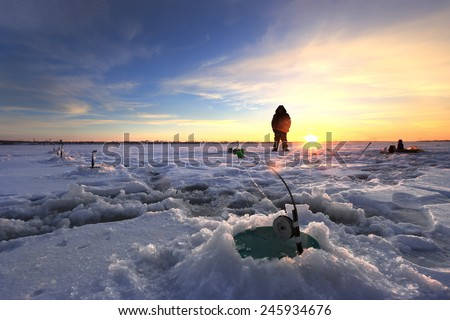 winter landscape fishermen on the ice of the river at sunset  - stock photo