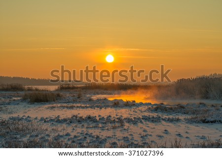 Winter landscape. Foggy winter sunset, colorful winter evening, bright sunshine over a river. Winter twilight at the river - stock photo