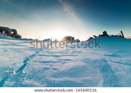 Winter landscape. Footprints in deep snow in a ghost town. - stock photo
