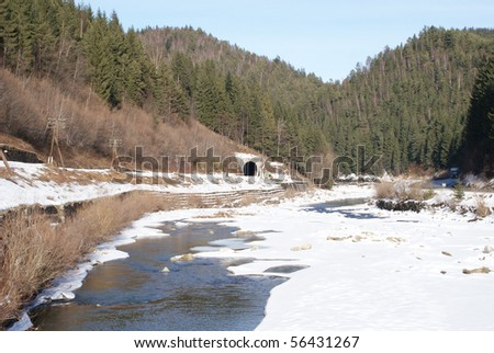 Winter landscape, frozen river, railway tunnel - stock photo