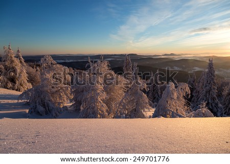 Winter landscape in mountains in the morning. The sun's rays and flare.