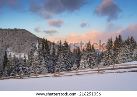 Winter landscape in the mountains. Sunny morning with beautiful clouds. Wooden fence on a mountain meadow in the forest. Christmas landscape