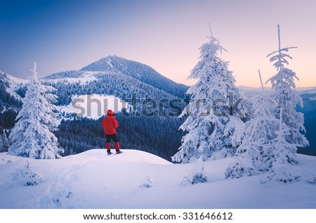 Winter landscape in the mountains. Tourist in a red jacket on a hill. Carpathians, Ukraine, Europe. Low contrast. Color toning - stock photo