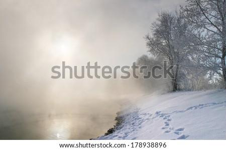 winter landscape misty morning on the river at sunrise - stock photo