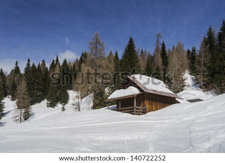winter landscape of mountain hut nestled in the snow - stock photo