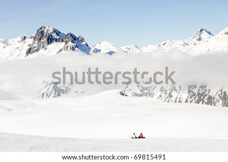 Winter landscape of mountains with resting snowboarders and blue cloudy sky, Saint Jean d'Arves, France